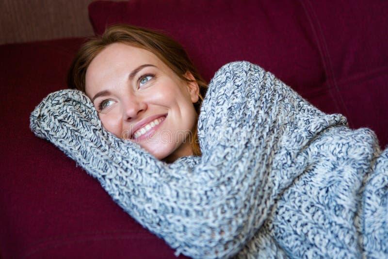 Retrato da mulher alegre na camiseta feita malha que encontra-se no sofá imagens de stock royalty free