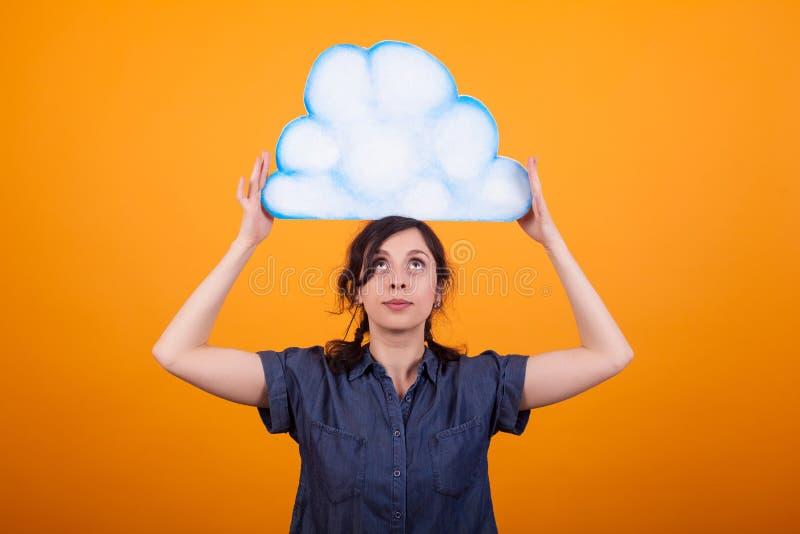 Retrato da mulher alegre que mantém e que olha em uma nuvem pensada no estúdio sobre o fundo amarelo fotos de stock