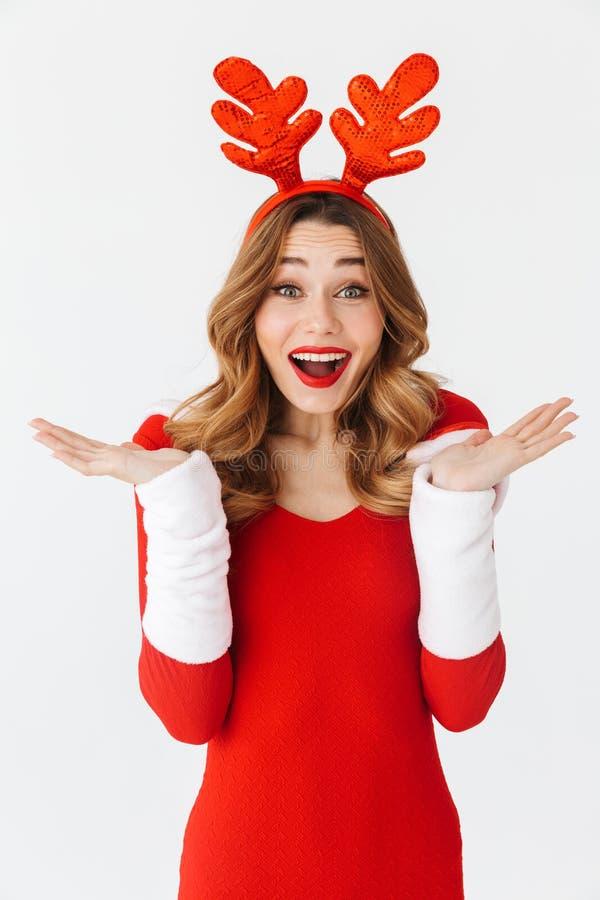 Retrato da mulher alegre 20s que veste as orelhas vermelhas do traje e dos cervos de Santa Claus que sorriem e que estão, isolado foto de stock royalty free