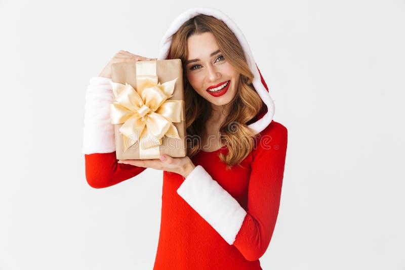 Retrato da mulher alegre 20s que veste o traje vermelho de Santa Claus que sorri e que guarda a caixa atual, isolado sobre o fund foto de stock royalty free