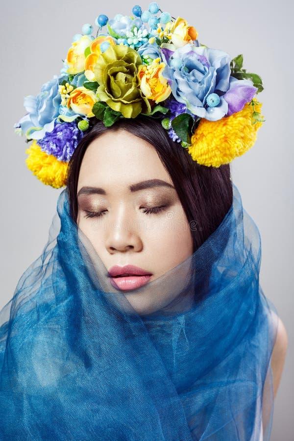 Retrato da mulher asiática atrativa com chapéu floral e o véu azul que levantam com os olhos fechados em claro - fundo cinzento fotos de stock