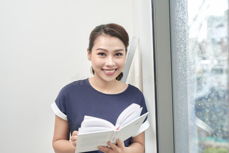 Retrato da mulher asiática atrativa que lê um livro perto da janela O estilo de vida relaxa o exame da educação que prepara o con fotografia de stock