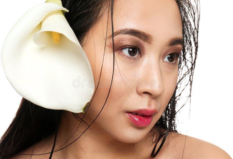 Retrato da mulher asiática bonita com a flor no fundo branco, close up foto de stock royalty free