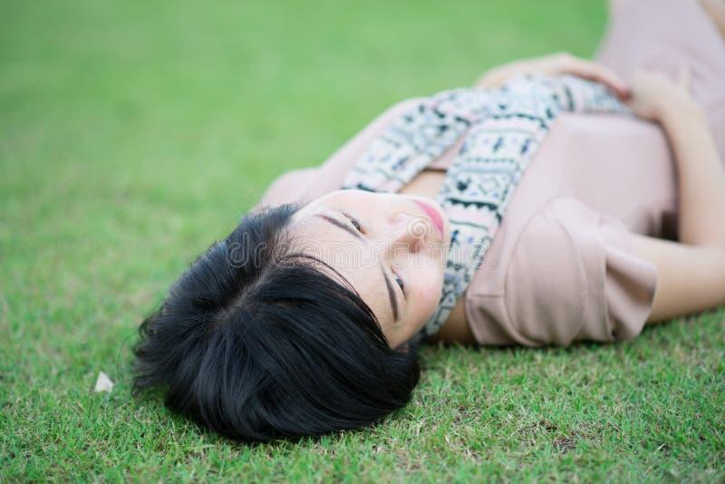 Retrato da mulher asiática bonita no relaxamento do parque exterior com sorriso feliz imagens de stock