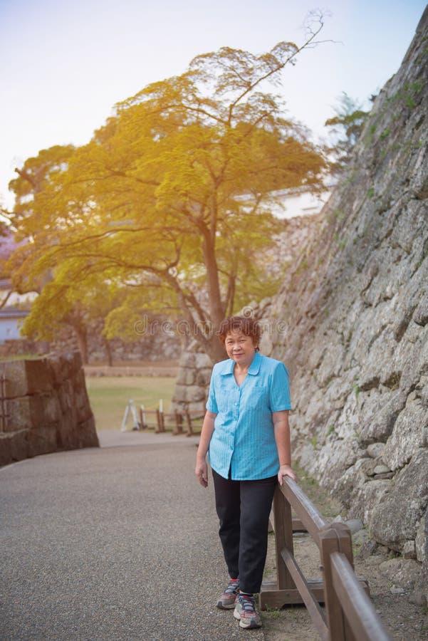 Retrato da mulher asiática mais idosa na camisa azul que está em japão GA fotos de stock