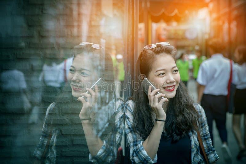 Retrato da mulher asiática mais nova que fala à manutenção programada toothy do telefone esperto fotos de stock