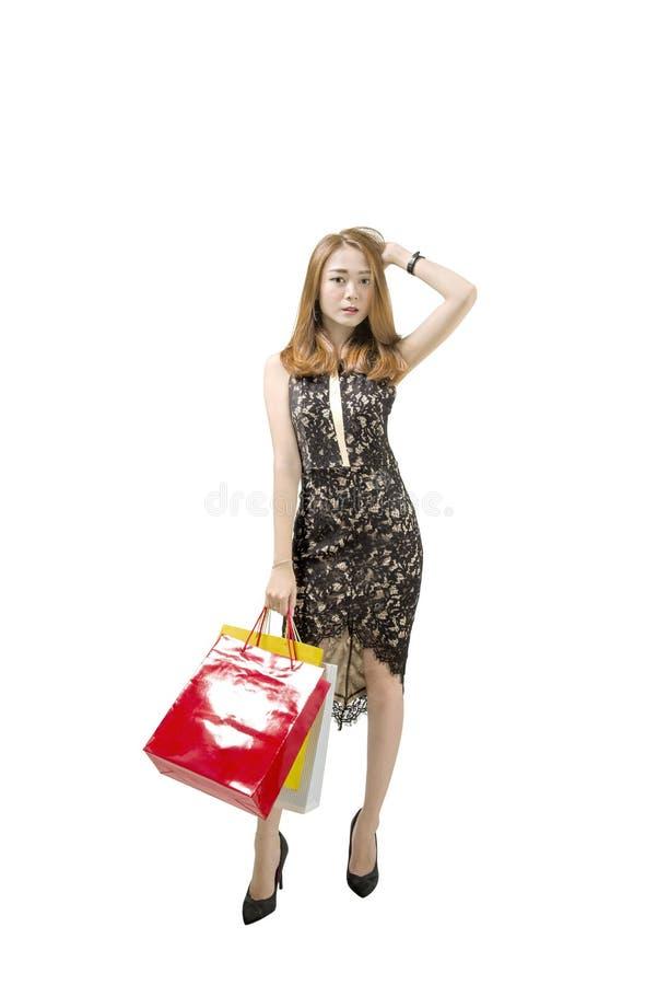 Retrato da mulher asiática no vestido preto que guarda o sta dos sacos de compras fotos de stock