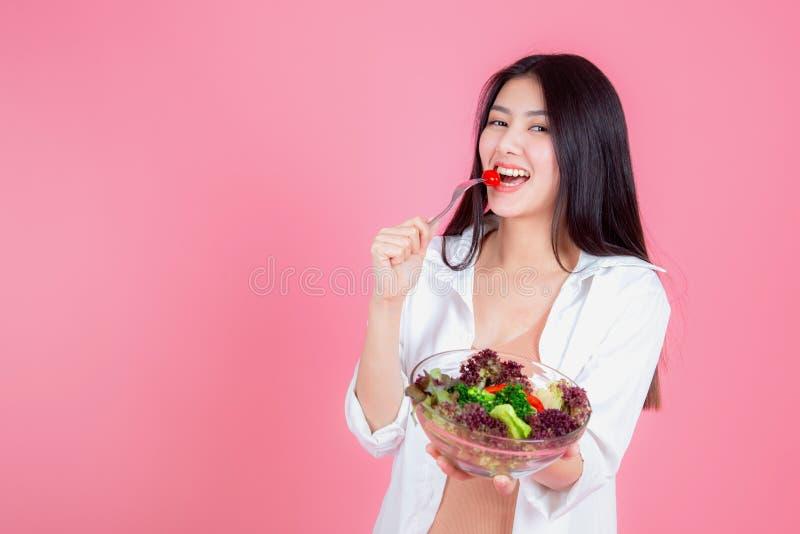Retrato da mulher asiática nova atrativa que come o legume fresco saudável foto de stock