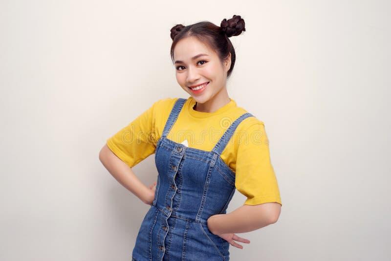 Retrato da mulher asiática nova bonita com bolos do cabelo e da vista flirty na câmera no fundo branco fotografia de stock royalty free