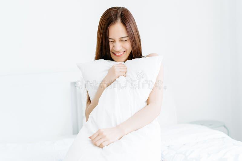 Retrato da mulher asiática nova bonita de sorriso que guarda um descanso e para fechar seu olho na cama Bom dia, dia novo, fim de foto de stock