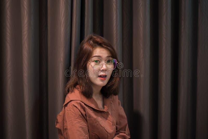 Retrato da mulher asiática nova com os óculos de sol no fundo da cortina imagem de stock royalty free