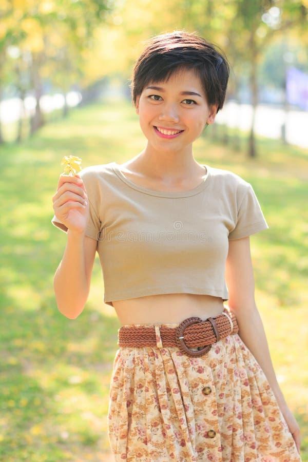 Retrato da mulher asiática nova e bonita que está na sagacidade do parque fotografia de stock royalty free