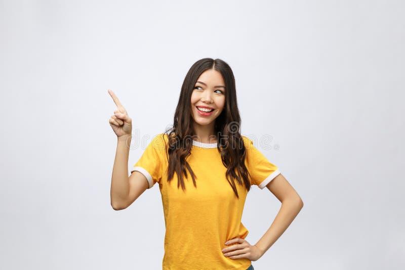 Retrato da mulher asiática nova feliz com ponto do dedo acima fotos de stock
