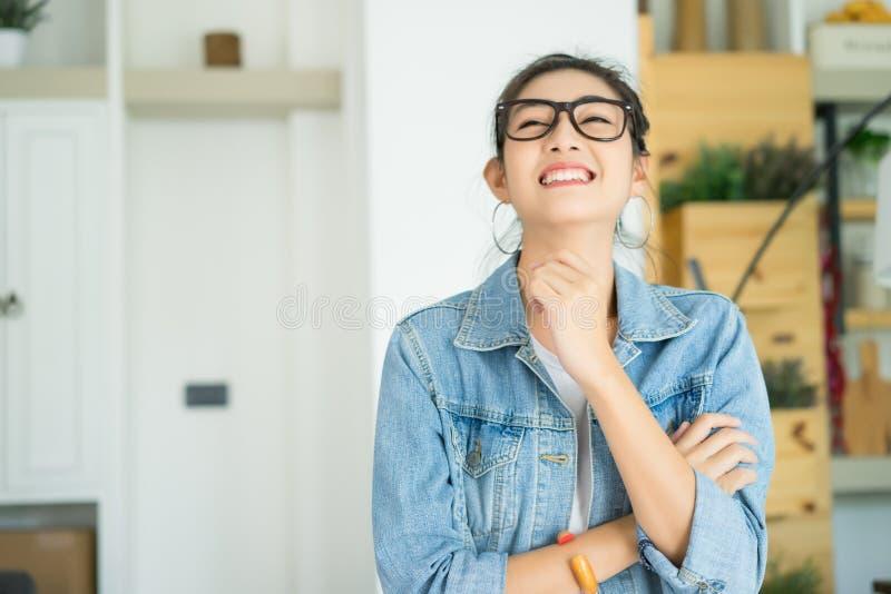 Retrato da mulher asiática nova feliz que ri contra em casa fora fotografia de stock royalty free