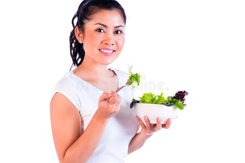 Retrato da mulher asiática nova que come a salada imagens de stock