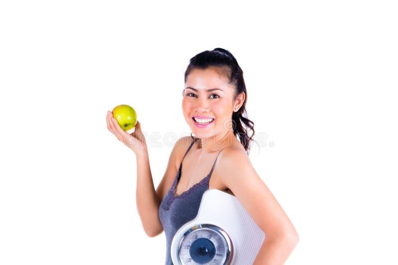 Retrato da mulher asiática nova que guarda a maçã e a escala fotos de stock