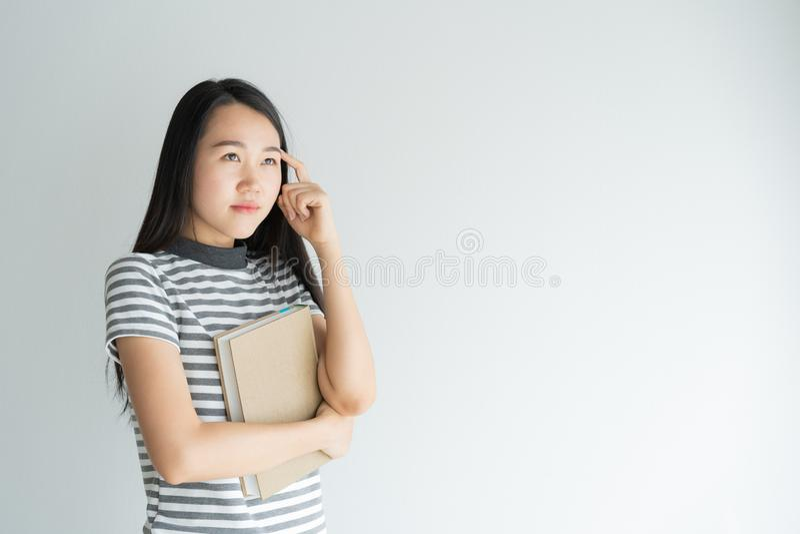 Retrato da mulher asiática que pensa e que guarda o caderno no fundo branco imagens de stock royalty free