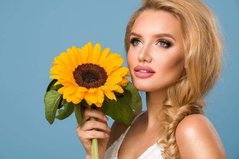 Retrato da mulher atrativa do verão com girassol à disposição fotografia de stock