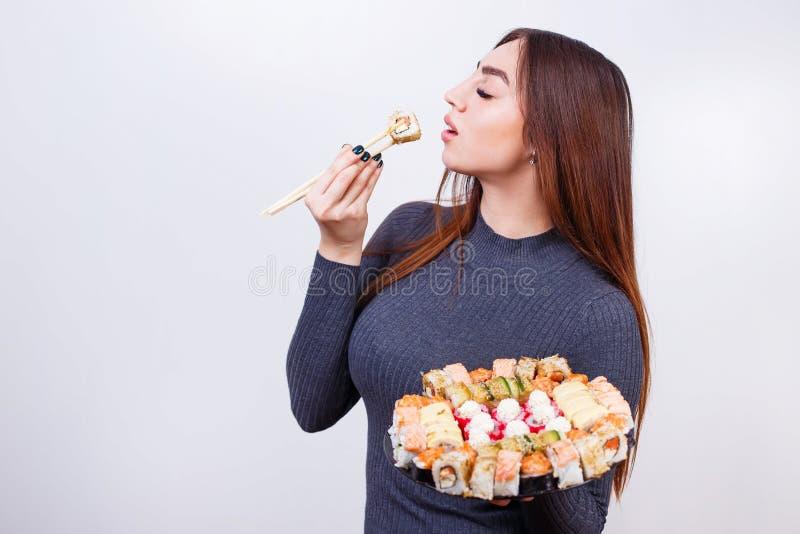 Retrato da mulher atrativa nova que come o sushi, tiro do estúdio sobre imagem de stock royalty free