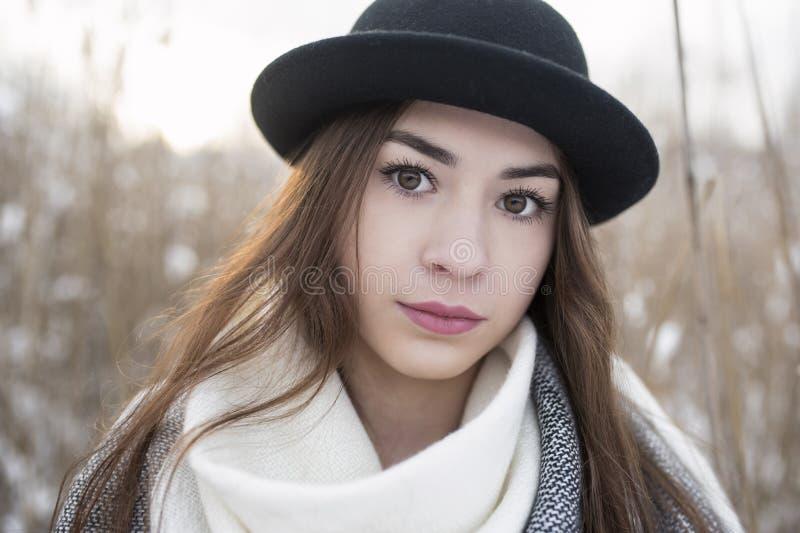 Retrato da mulher da beleza com os olhos marrons grandes, e chapéu de jogador sobre, no cenário do inverno fotografia de stock