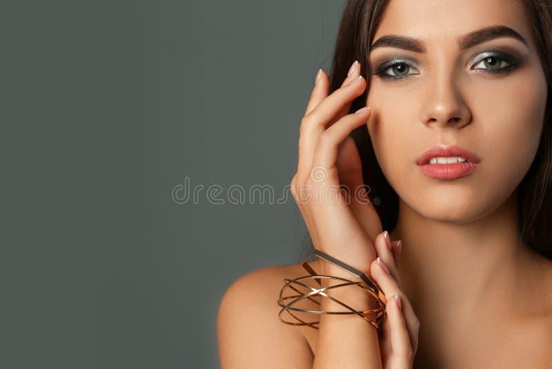 Retrato da mulher bonita com composição à moda no fundo cinzento fotos de stock
