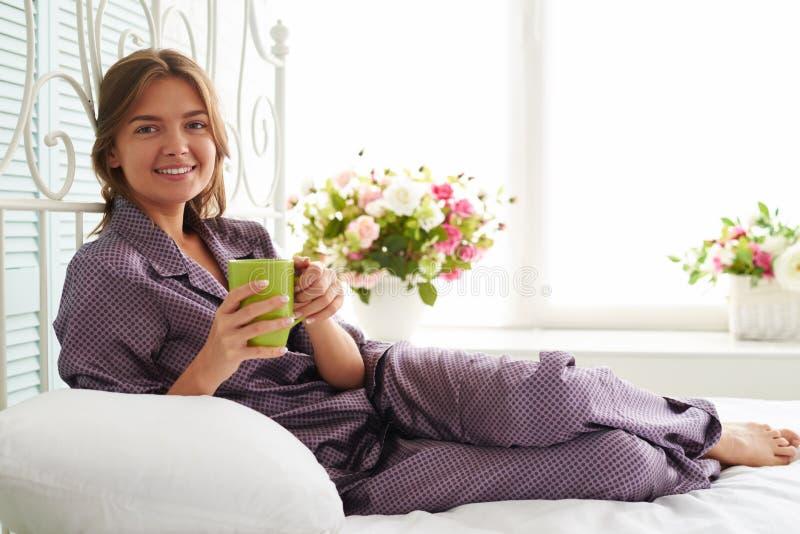 Retrato da mulher bonita de sorriso nos pijamas na cama com um copo imagens de stock royalty free
