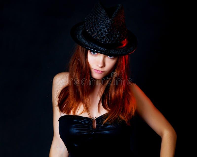 Retrato da mulher bonita elegante em um vestido e em um chapéu pretos Fundo preto imagem de stock royalty free