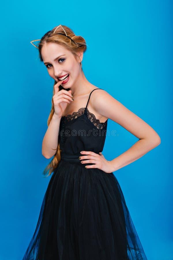 Retrato da mulher bonita no fundo azul, jovem senhora que levanta no partido, disfarce, carnaval, dedo de mordedura desgastar foto de stock