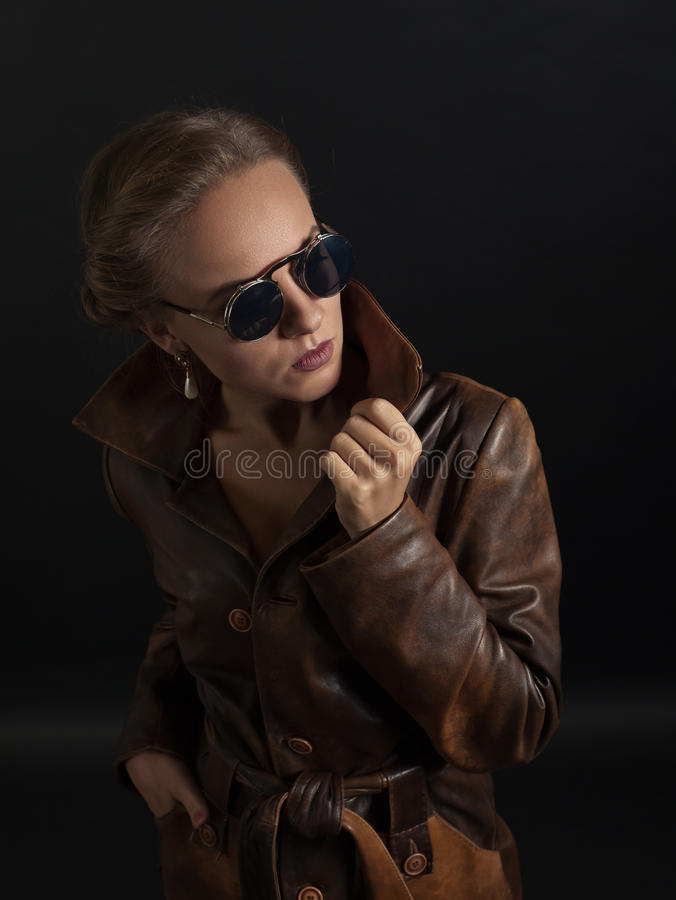 Retrato da mulher bonita no revestimento e em óculos de sol de couro marrons fotos de stock royalty free