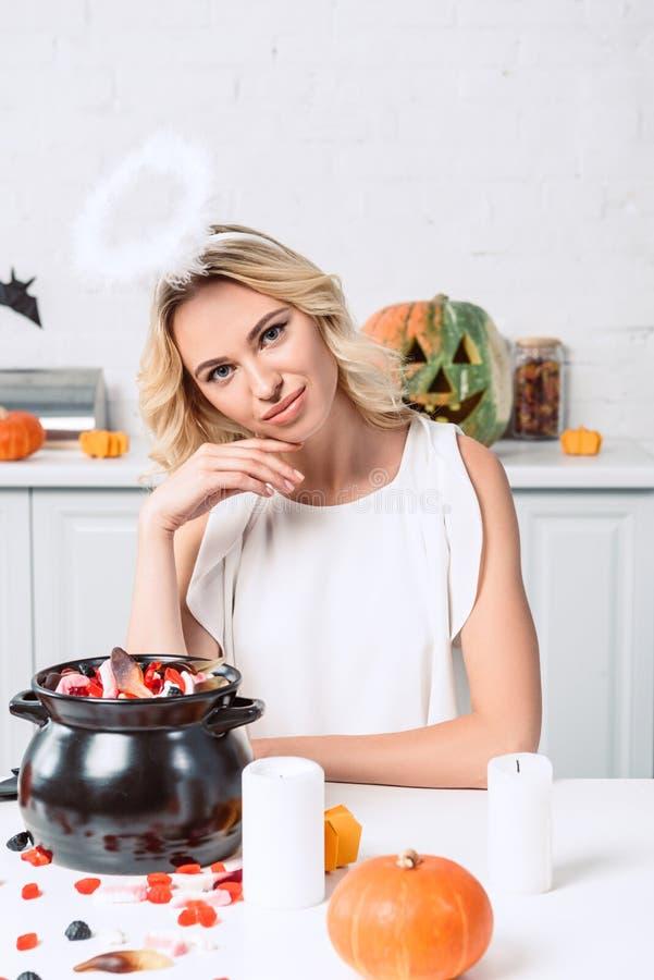 retrato da mulher bonita no traje do anjo que senta-se na tabela com os doces no potenciômetro preto foto de stock royalty free