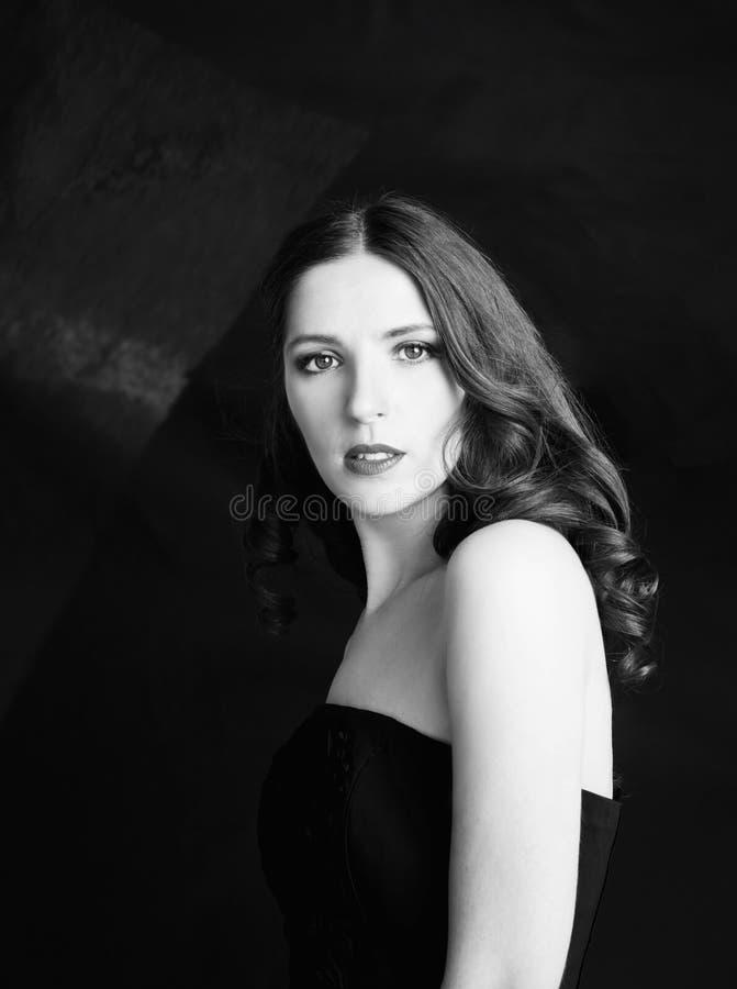 Retrato da mulher bonita no vestido preto com cabelo encaracolado - no fundo preto fotografia de stock
