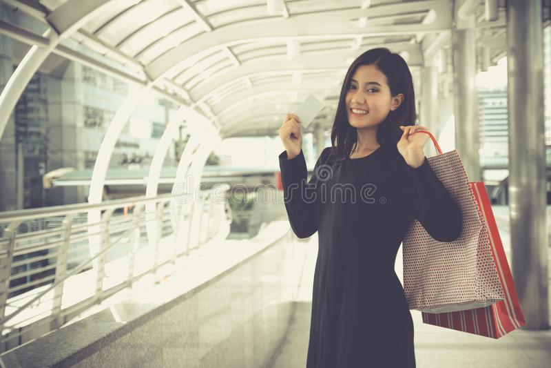 Retrato da mulher bonita nova de sorriso que guarda sacos de compras fotografia de stock