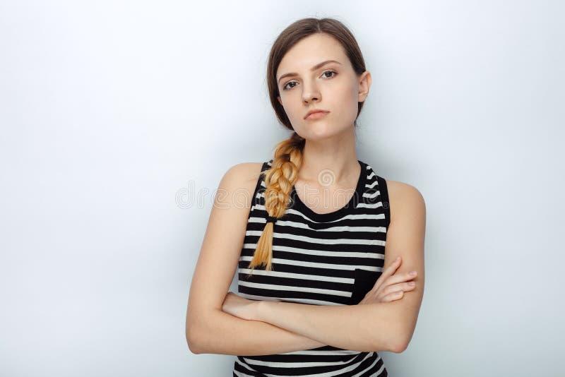 Retrato da mulher bonita nova impertinente séria em camisa listrada que levanta com os braços cruzados para os testes modelo cont fotos de stock