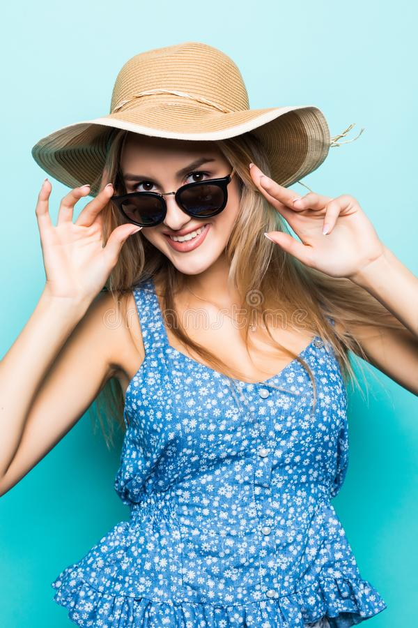 Retrato da mulher bonita nova no chapéu e nos óculos de sol do verão no fundo azul fotografia de stock