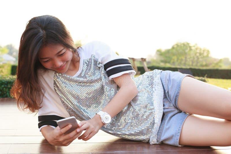 Retrato da mulher bonita nova que encontra-se e que lê o texto em smar fotografia de stock