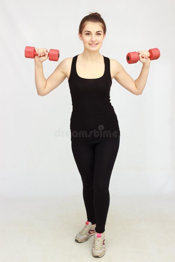 Retrato da mulher bonita nova que faz exercícios físicos com pesos imagem de stock royalty free
