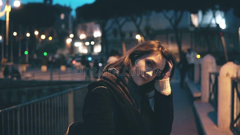Retrato da mulher bonita nova que olha a câmera e que faz acima do cabelo As voltas da menina, vão afastado na cidade da noite imagens de stock