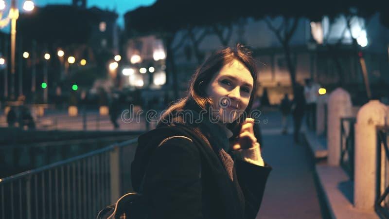 Retrato da mulher bonita nova que olha a câmera e que faz acima do cabelo As voltas da menina, vão afastado na cidade da noite foto de stock royalty free