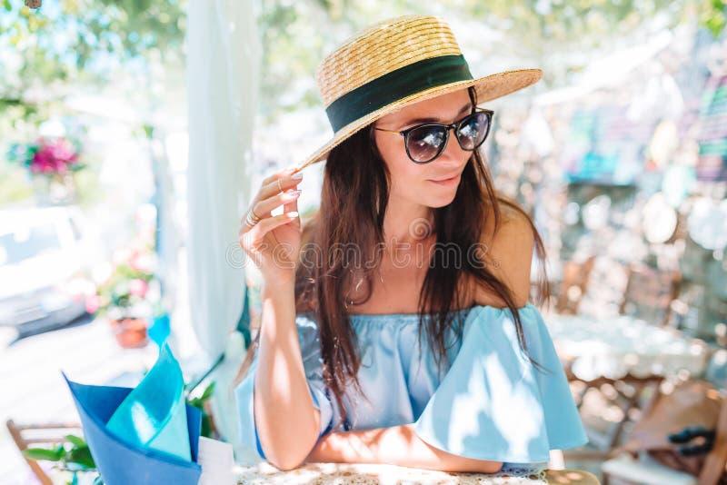 Retrato da mulher bonita nova que senta-se em um caf? bebendo exterior do caf? imagem de stock