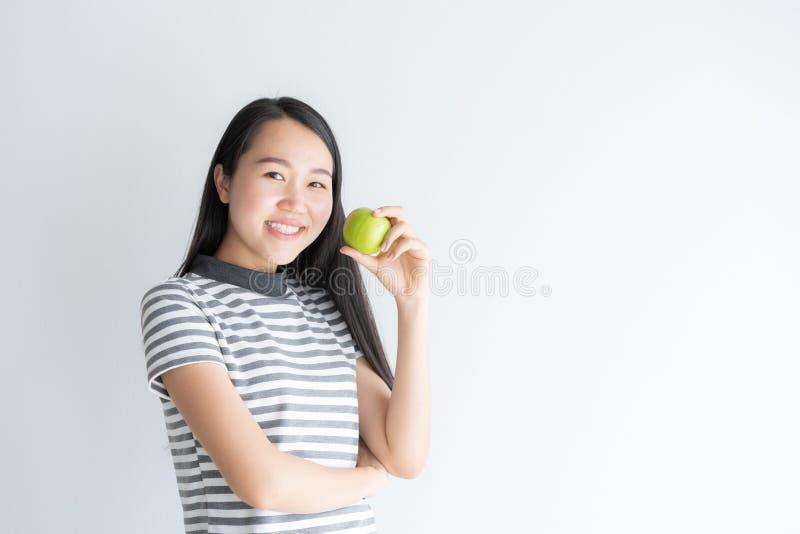 Retrato da mulher bonita nova uma câmera de sorriso e de vista Posição longhair do preto bonito asiático da menina sobre o branco imagem de stock