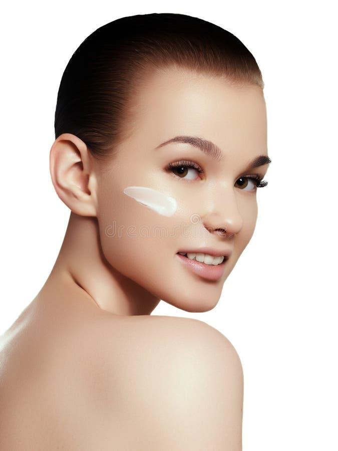 Retrato da mulher bonita que aplica algum creme a sua cara para cuidados com a pele fotos de stock