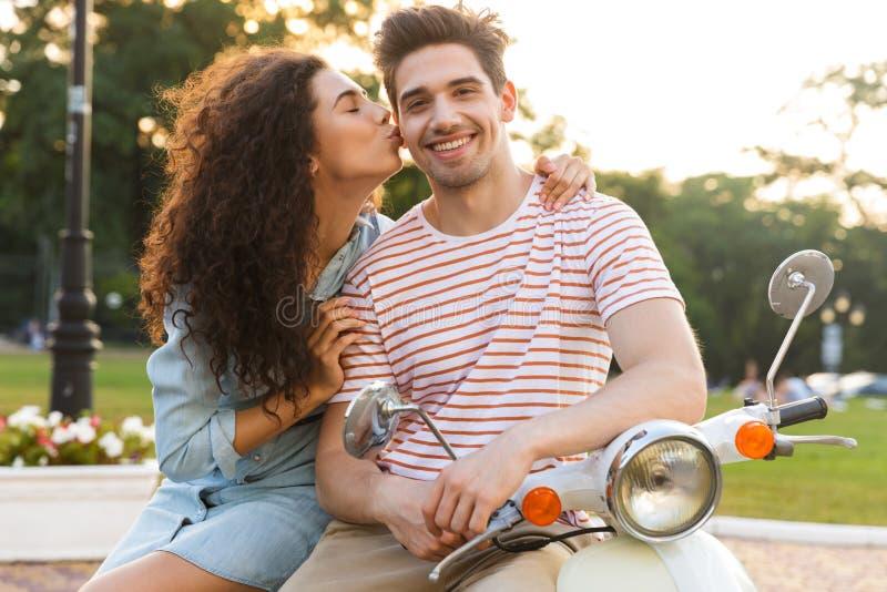 Retrato da mulher bonita que beija o homem caucasiano no mordente ao sentar-se no velomotor fotografia de stock royalty free