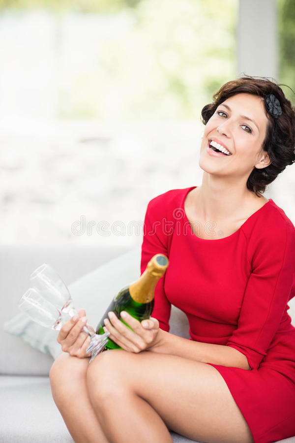 Retrato da mulher bonita que guarda a garrafa e o vidro do champanhe foto de stock
