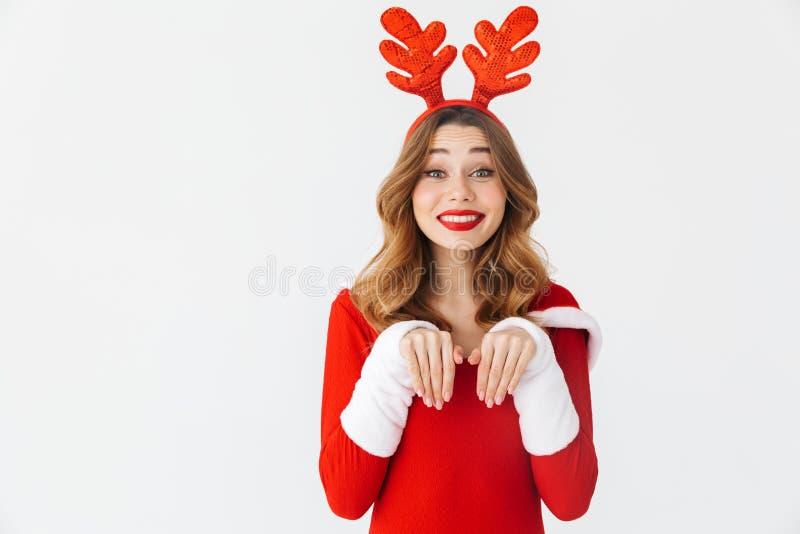 Retrato da mulher bonita 20s que veste as orelhas vermelhas do traje e dos cervos de Santa Claus que sorriem e que estão, isolado fotos de stock