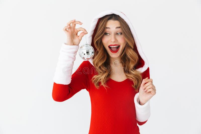 Retrato da mulher bonita 20s que veste o traje vermelho de Santa Claus que sorri e que guarda a bola da árvore de Natal, isolado  imagem de stock