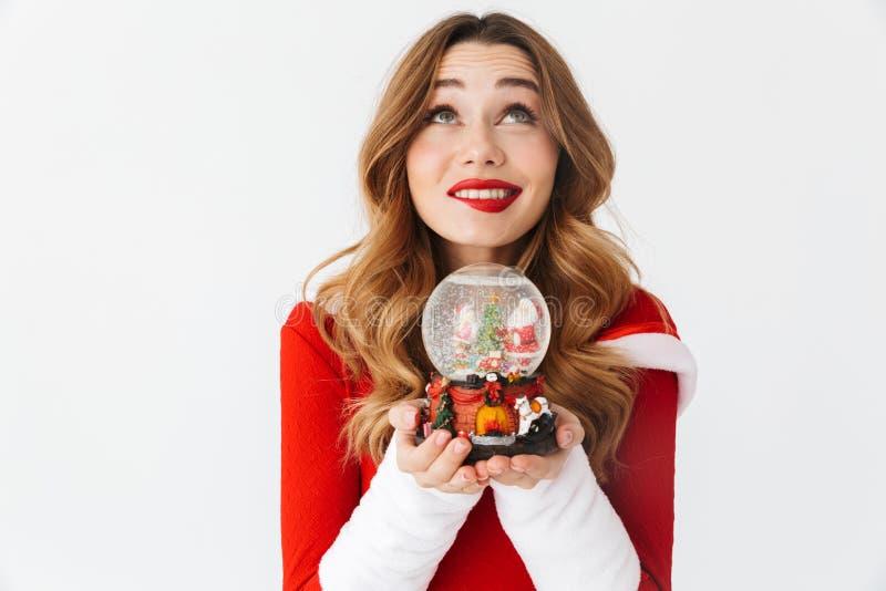 Retrato da mulher bonita 20s que veste o traje vermelho de Santa Claus que sorri e que guarda a bola da neve do Natal, isolado so foto de stock royalty free