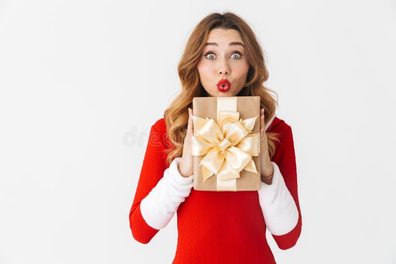Retrato da mulher bonita 20s que veste o traje vermelho de Santa Claus que sorri e que guarda a caixa atual, isolado sobre o fund imagem de stock
