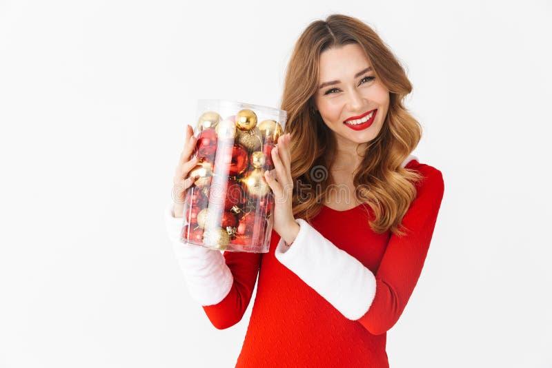 Retrato da mulher bonita 20s que veste o traje vermelho de Santa Claus que sorri e que guarda decorações da árvore de Natal, isol foto de stock royalty free