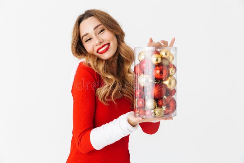 Retrato da mulher bonita 20s que veste o traje vermelho de Santa Claus que sorri e que guarda decorações da árvore de Natal, isol foto de stock