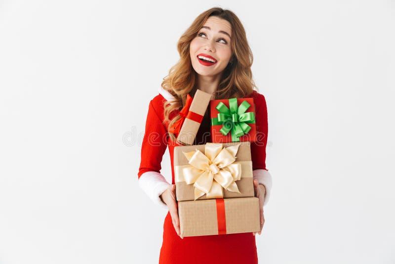 Retrato da mulher bonita 20s que veste o traje vermelho de Santa Claus que sorri e que guarda o grupo das caixas atuais, isolado  fotos de stock royalty free